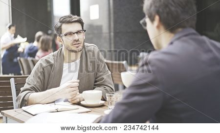 Two Friends Are Having A Conversation At Table Of The Cafe Outdoors. A Man Dressed In A Jacket Weari