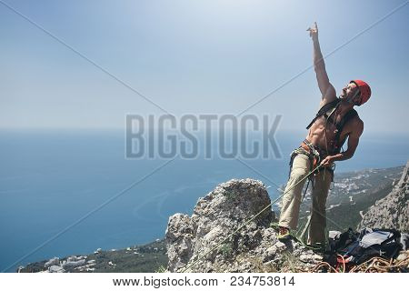 Man Rock Climber Stands On The Top Of The Cliff And Belays A Partner And Shows Up To The Sky By The