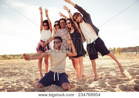 Image of excited young friends walking outdoors on the beach make selfie by mobile phone.