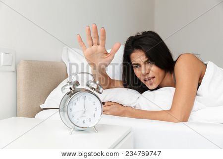 Image of angry woman 20s lying in bed on pillow and turning off ringing alarm clock on nightstand