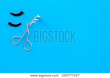 Curled And Thick Eyelashes. False Eyelashes And Eyelash Curler On Blue Background Top View.