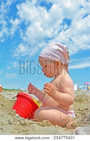 Cute Little Girl Play With Sand On Beach At Sunny Day