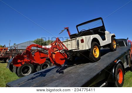 Dalton, Minnesota, Sept 8, 2017: A Restored Willys Jeep Hooked To A Plow On A Flat Bed Trailer Will