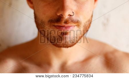 Sensual guy with a beautiful skin and a piercing on his nose