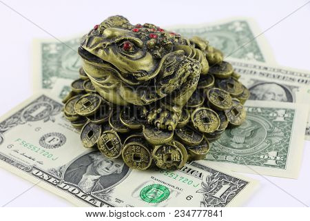Chinese Feng Shui Lucky Frog, Toad With Red Eyes Sits On Coins And Dollar Bills. Symbol For Abundanc