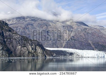 The Scenic View Of A Mountainous Coastline With A Glacier In Glacier Bay National Park (alaska).