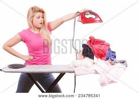 Household Duties, Domestic Chores Concept. Shocked Woman Holding Iron About To Do Ironing