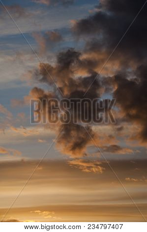 Pale Blue Sky With Dark Fluffy Clouds