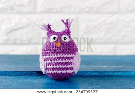Cute Handmade Purple With Pink Knitted Owl Toy On A Brick Wall Background, Copy Spase
