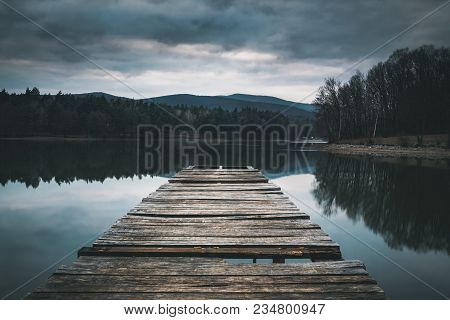 Mole (pier) On The Lake.  Wooden Bridge In Forest In Spring Time With Blue Lake. Lake For Fishing Wi