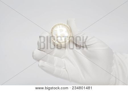Hand In White Glove Holds Golden Bitcoin Crypto Currency Isolated On White.mining Concept.