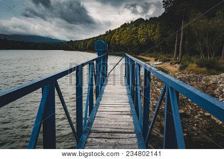 Mole (pier) On The Scandinavian Lake With Motorboat On Side And Misty Hills. Blue Wooden Bridge In F