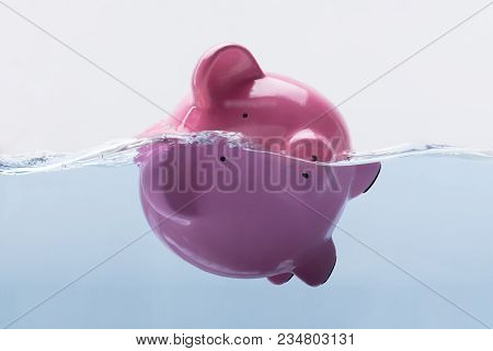 Close-up Of A Pink Piggy Bank Drowning In Water