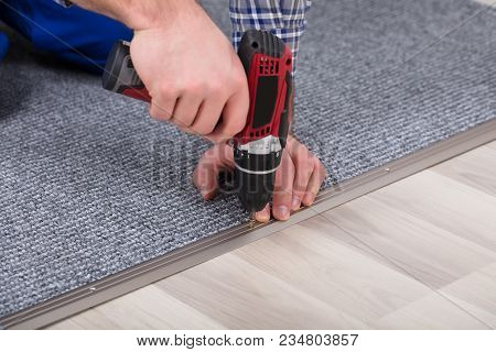 Carpet Fitter Installing Carpet With Wireless Screwdriver