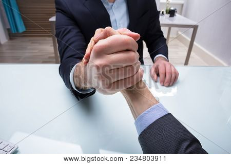 Close-up Of Two Businessmen Competing In Arm Wrestling On Desk At Workplace