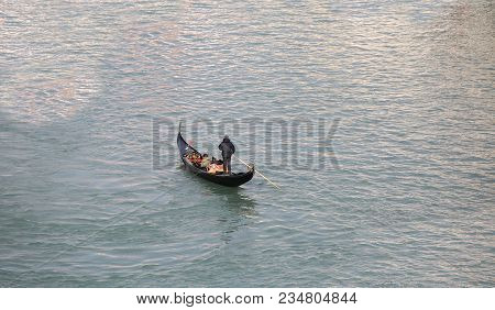 Lonely Gondolier With Black Gondola In The Water Of Grand Canal In Venice Italy