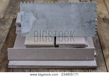 Laying And Cutting Tiles. Tools And Building Materials At A Working Position. Tiles For Industrial A