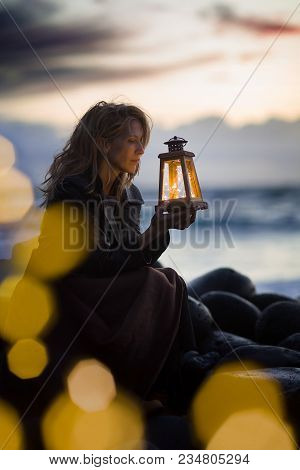 Evening After Sunset At The Beach, Blonde Woman Sits With Lantern Beside The Sea, Light Bokeh