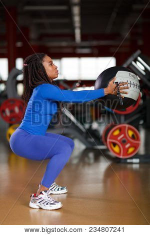 African Athletic Woman In Blue Sportswear Crutches With A Big Heavy Boll At The Gym. Fitness Woman I