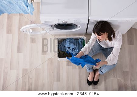 Elevated View Of Young Woman Looking At Cloth In Laundry Room