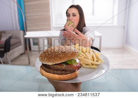 Young Woman Refusing Burger And French Fries While Eating Fruit At Home