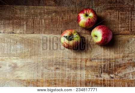 Still life with red autumnal apples on rustic wooden table; seen from above