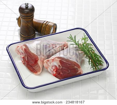 raw lamb shank isolated on white butcher tray