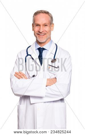 Portrait of happy senior doctor with folded arms isolated on white background. Confident male doctor in a labcoat and stethoscope looking at camera. Portrait of handsome mature doctor.