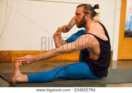 Springfield, Or - March 11, 2018: Yoga Instructor Ben Wilkinson Practicing A Pose During A Class At