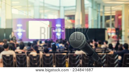 Microphone Over The Abstract Blurred Photo Of Conference Hall Or Seminar Room With Speakers On The S