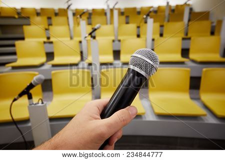 Closeup male hand with black microphone against auditorium.