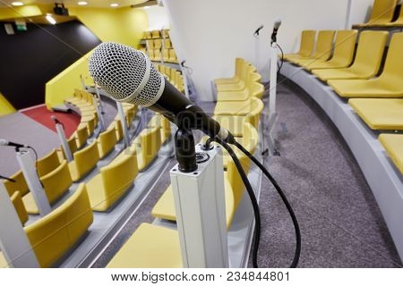 Closeup microphone in auditorium with chairs and micriphones.