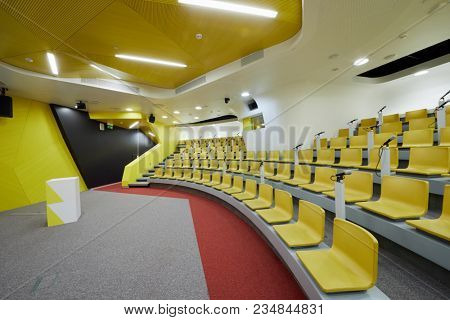 Interior of auditorium with chairs and microphones, stand for speaker.