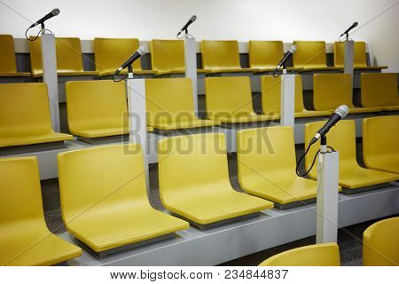 Yellow chairs and microphones in auditorium.