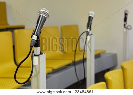 Three microphones in auditorium with yellow chairs.
