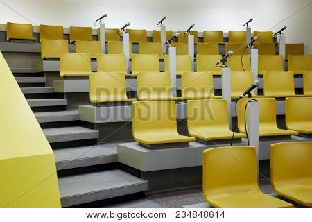 Auditorium with yellow chairs and microphones.