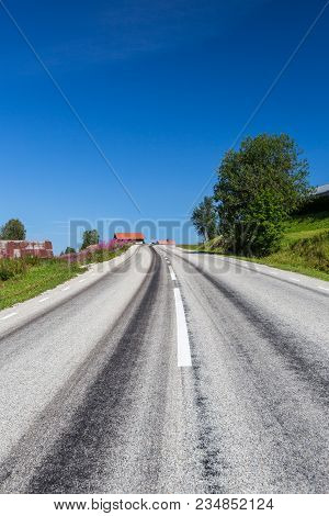 Straight Gray Asphalt Road In Country Side With Old Buildings And Blue Sky.