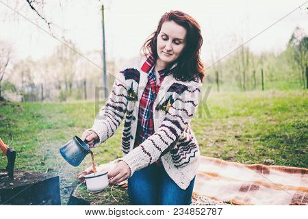A Girl Is Drinking Coffee By The Fire.