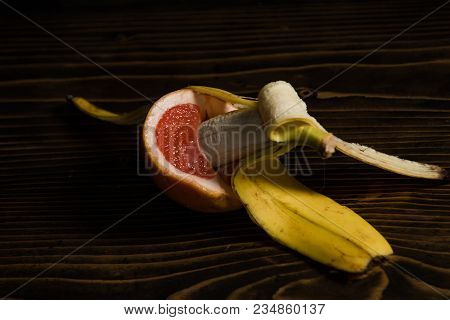 Sex. Sexual Intercourse Of Banana With Yellow Peel In Red Grapefruit On Wooden Background, Fruit Lov