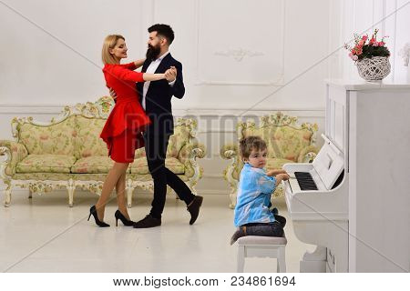 Rich Parents Enjoy Parenthood. Boy Adorable Try To Play Piano Musical Instrument, While Parents Danc
