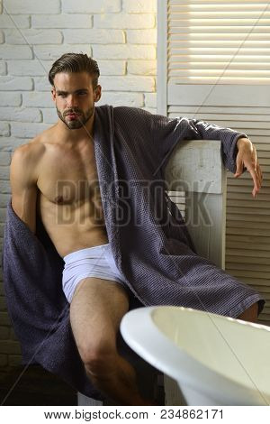 Fitness, bodycare, wellness. Man with fit body in underwear, bathrobe, fashion. Sexy macho with six pack, ab, torso in bathroom, fitness. Health, bodycare, hygiene. Fashion, home wear, underwear. poster