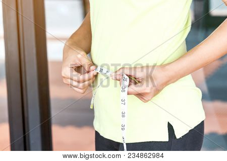 Woman With Tape Measure Around Body Waist