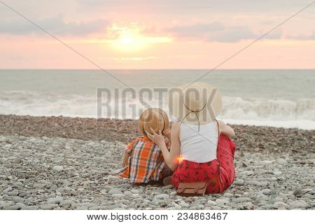 Mom And Son Sitting On The Beach And Admire The Sunset. Back View