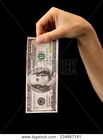 One Hundred Dollars In A Hand On A Black Background .