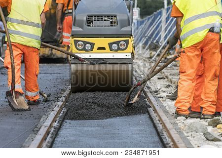Steamroller Workers Construct Asphalt Road And Railroad Lines