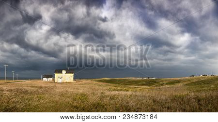 Panorama of an old fisherman's cottage on the clifftop with dramatic storm clouds. Havre Abert, Ilse de la Madeleine, otherwise known as the Magdalen Islands, Canada