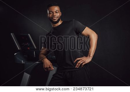 Handsome Young Athletic African American Man Leaning At Treadmill And Smiling At Camera