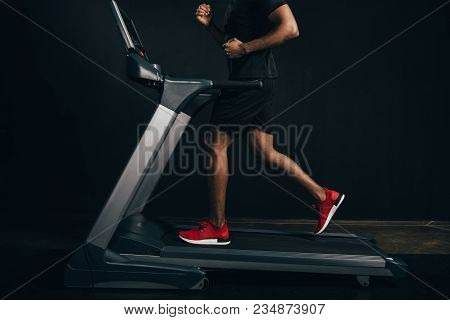 Cropped Shot Of African American Sportsman Running On Treadmill On Black