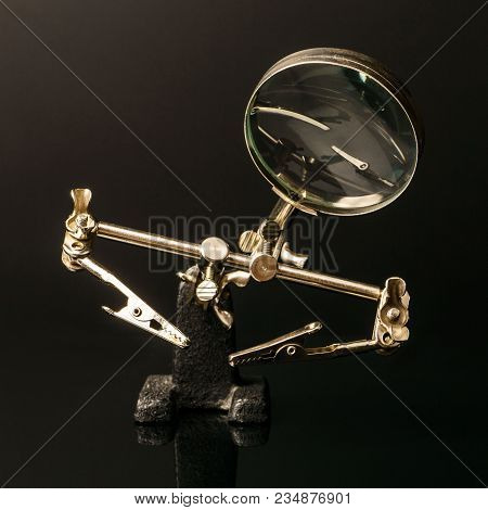 The Third Hand Device With Clamps And Magnifier For Holding Small Parts During Soldering On Black Ba