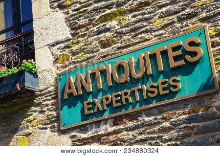 Closeup Signboard Of Antiquites Expertises Written In Golden On Green Banner Against Wooden Brick Wa